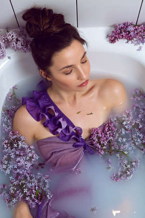 sexy fashionable woman in swimsuit dress lies in a white bath with milk and lilac flowers