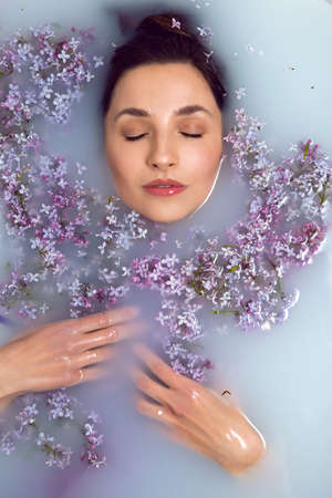 woman lies in a white bath with milk and lilac flowers