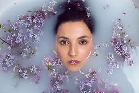 fashionable woman lies in a white bath with milk and lilac flowers