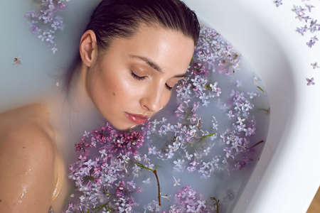 woman lies in a bathtub with milk and lilac flowers during a spa 免版税图像