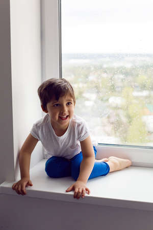 boy in a white tank top and blue pants sits on a window in rainy weather
