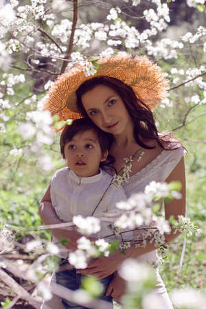 woman in pink clothes and a straw hat stands with a child in a white shirt in a blossoming apple orchard 版權商用圖片