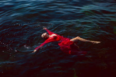 woman swims in the sea in a red long dress with sunglasses in summer