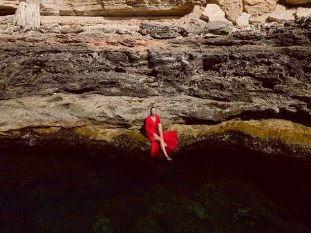 woman sits on a yellow rock near the green sea 免版税图像