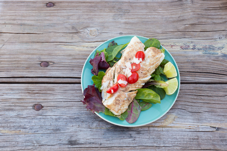 cebolla blanca: Overhead shot of grilled cod fish on a plate with spring mix greens, lime wedges, cherry tomatoes, and white onion Foto de archivo