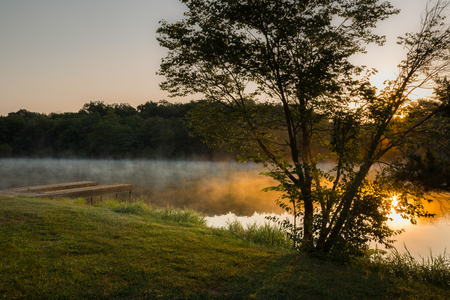 cold air: A landscape shot of a warm lake steaming in the cold air of a fall sunrise
