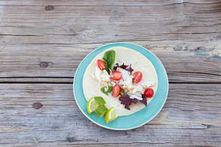 cebolla blanca: Overhead shot of a cod fish taco with spring mix greens, white onion, cherry tomatoes and lime wedges