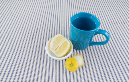 lemon water: An overhead close up shot of hot lemon water in a blue coffee cup Stock Photo