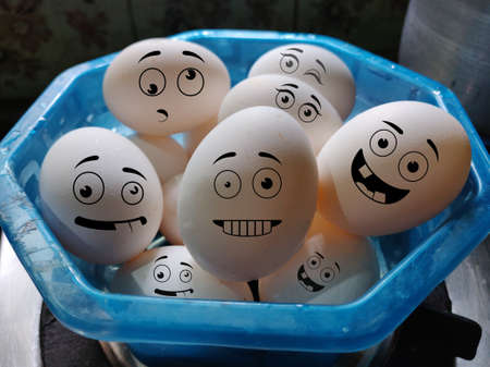 Happy and crazy faces of White Chicken eggs in a basket Archivio Fotografico