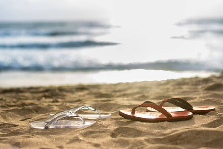 Couple's flip flop facing each other on beach at sunset