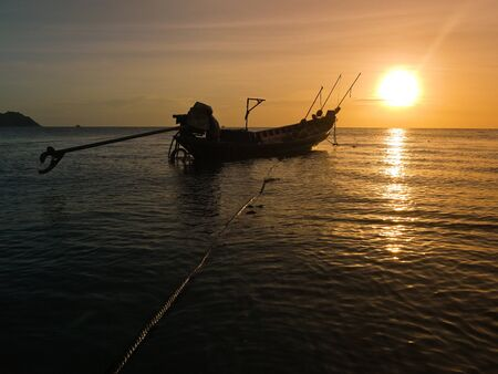 Long tail boat and sunset enar koh phangan, thailand photo