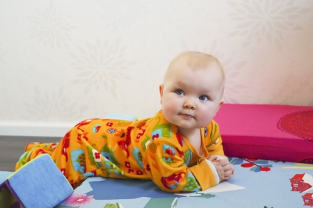 Cute 8 months old baby lying on bed in casual home environment