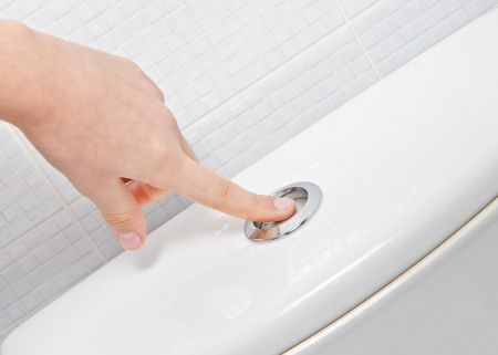 flushing: finger pushing button and flushing toilet