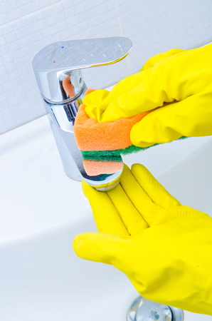 doing chores: woman doing chores in bathroom at home cleaning sink and faucet with spray detergent