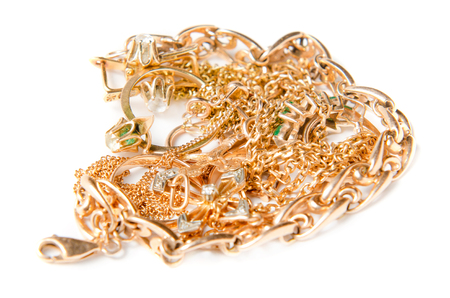 scrap gold: Isolated pile of gold jewelry on white background chains necklaces bracelets earrings rings and other scrap gold.