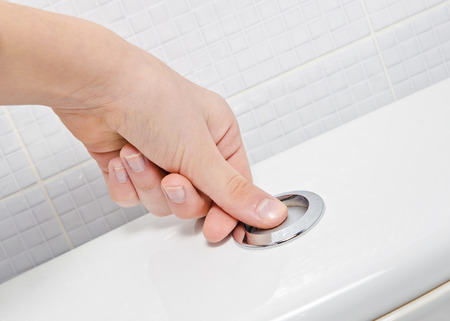 inodoro: dedo presionando el botón y el lavado higiénico Foto de archivo
