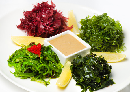 iodine: Plate with salad Chuka Seaweed with lemon and peanut sauce on an isolated white background