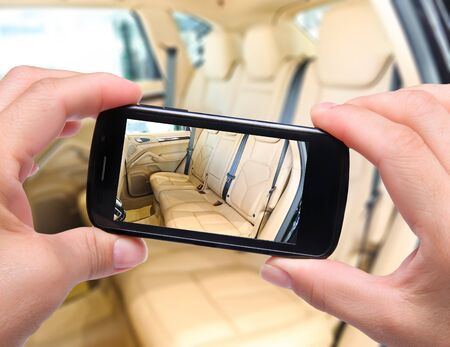 Hands taking photo car interior with smartphone photo