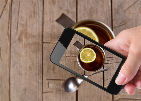 stimulated: Hands taking photo cup tea with smartphone