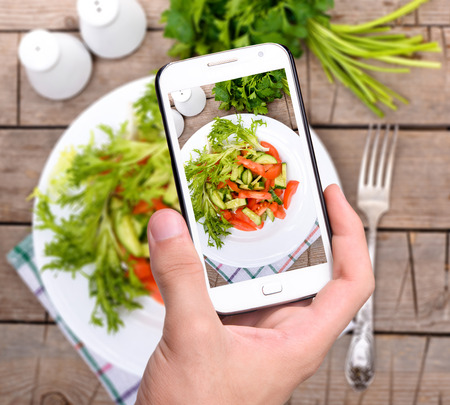 background photo: Hands taking photo vegetable salad with smartphone