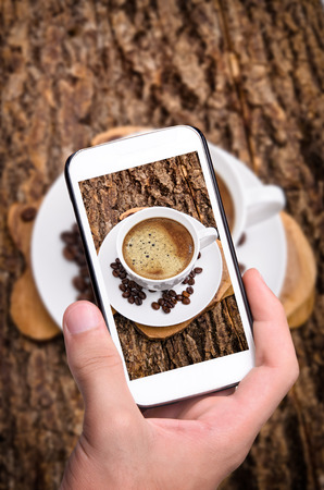 Hands taking photo coffee cup with smartphone. photo
