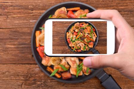 comida: Manos que toman carne de fotos con verduras con tel�fono inteligente.