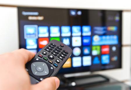 スマート テレビと手を押すとリモコン。 写真素材