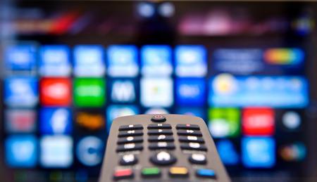 スマート テレビと手を押すとリモコン。 写真素材 - 40251694