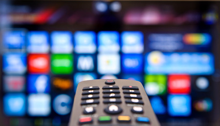 control panel: Smart TV y mano presionando control remoto. Foto de archivo