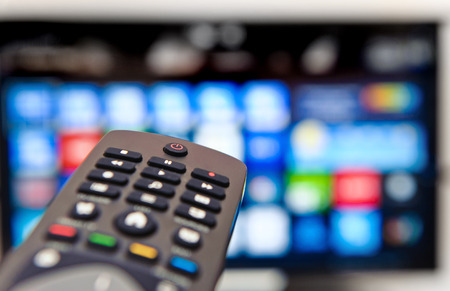 tv panel: Smart tv and hand pressing remote control.