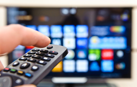 panel de control: Smart TV y mano presionando control remoto. Foto de archivo