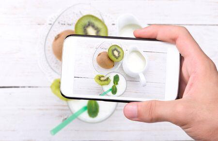 tomando refresco: Manos que toman la foto con el tel�fono inteligente batido.