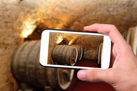 taking photo: Hands taking photo old wine barrels with smartphone.