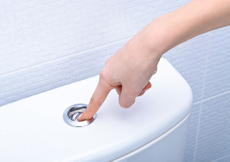 finger pushing button and flushing toilet