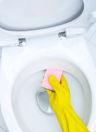 wc: Hands on yellow gloves cleaning a WC
