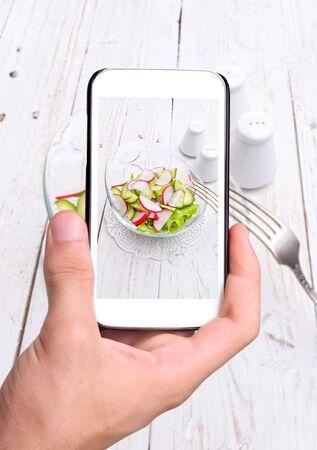 kitchen detail: Hands taking photo radish salad with smartphone