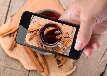 tomando refresco: Manos que toman la foto vino caliente con el teléfono inteligente