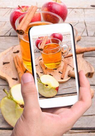 cider: Hands taking photo cider with smartphone