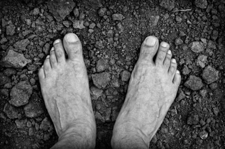 pretty feet: Bare foots over dry soil Stock Photo