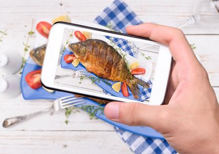 tomando refresco: Manos que toman pescado foto con el tel�fono inteligente.