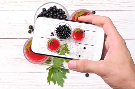 tomando refresco: Manos que toman la foto bebida grosella con el teléfono inteligente.