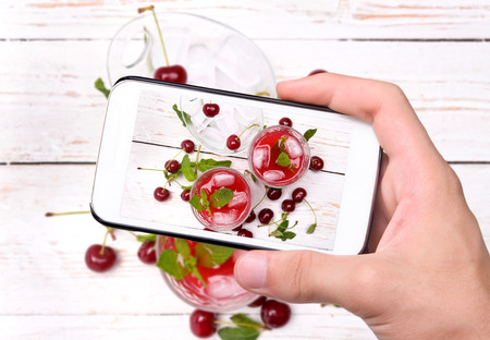tomando refresco: Manos que toman la foto bebida cereza con el teléfono inteligente. Foto de archivo