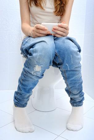 person sitting: Joven sentado en el cuarto de ba�o o aseo inodoro usando el tel�fono en las manos.