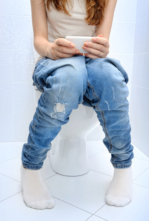 Young woman sitting on bathroom or wc toilet bowl using phone in hands.