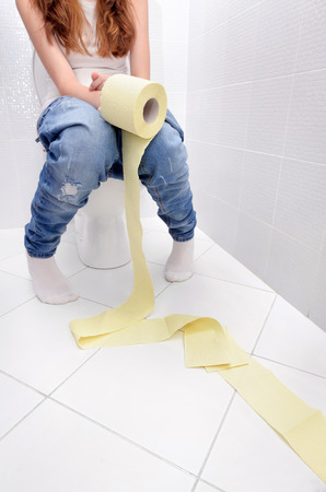 toilet roll: Close-up of woman on toilet. Stock Photo