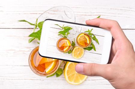 tomando refresco: Manos que toman la foto t� helado con lim�n con el tel�fono inteligente. Foto de archivo