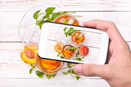 tomando refresco: Manos que toman la foto t� helado con el melocot�n con el tel�fono inteligente.