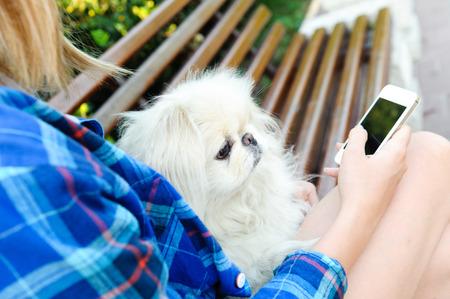 celula animal: Muchacha que usa un tel�fono celular al aire libre. Foto de archivo