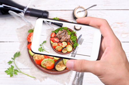 Hands taking photo grilled rib with grilled vegetables with smartphone. Фото со стока