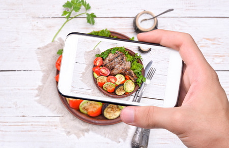 meat food: Hands taking photo grilled rib with grilled vegetables with smartphone. Stock Photo